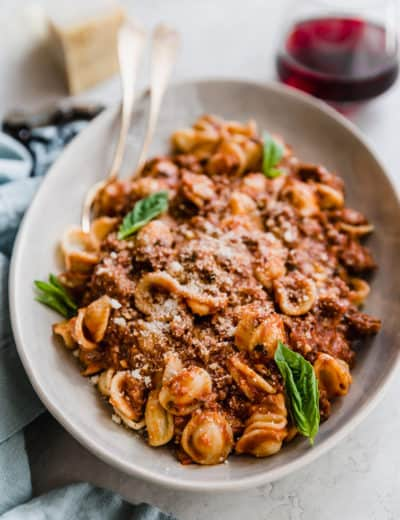 A bowl of pasta with bolognese sauce and fresh basil leaves.