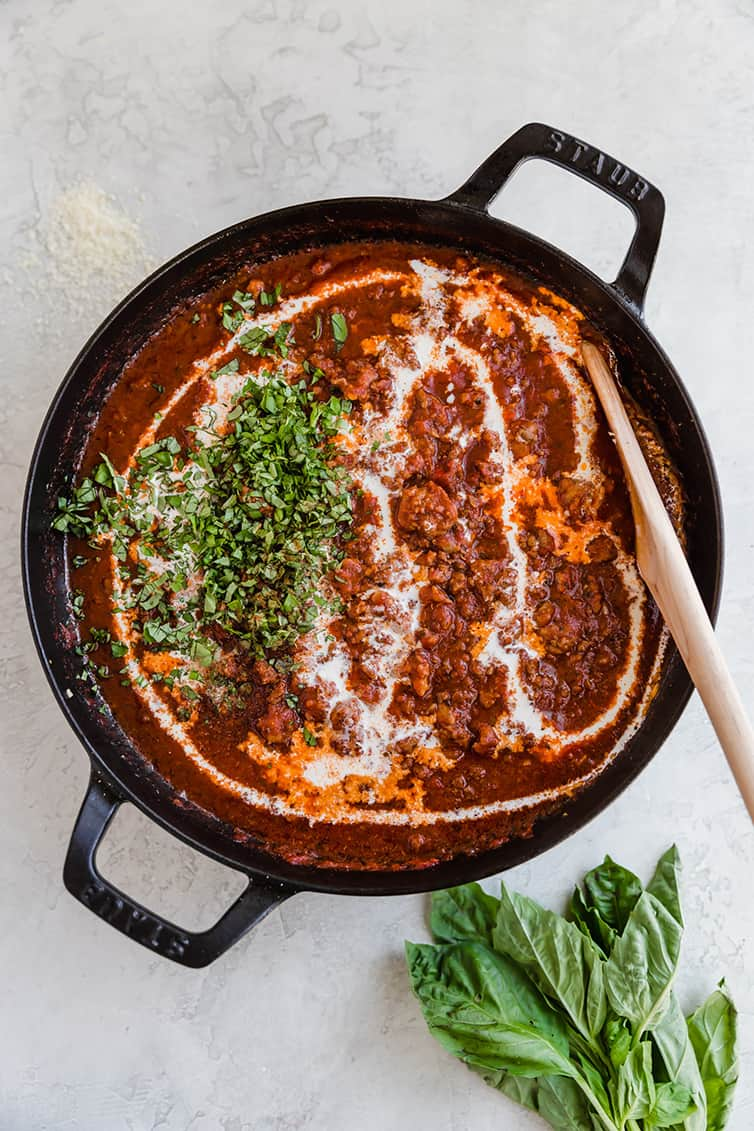 A pan of bolognese sauce with cream and fresh basil added.