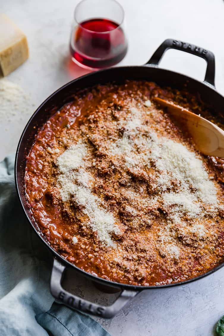 A pan of bolognese sauce with grated Parmesan cheese added.