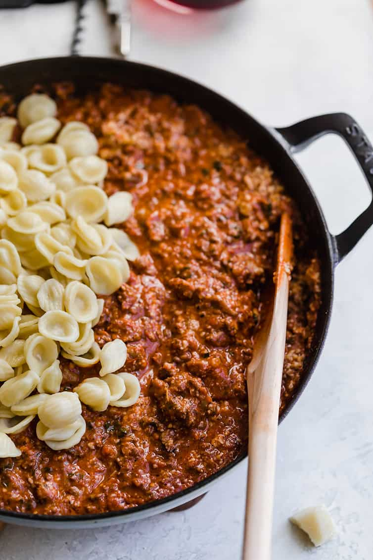 Orecchiette pasta mixed into a pan of bolognese sauce.