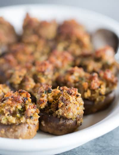 A serving platter full of sausage stuffed mushrooms.