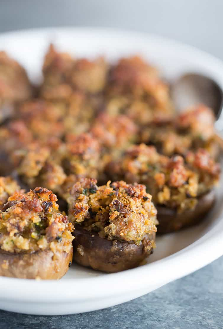 A serving platter full of sausage stuffed mushrooms.