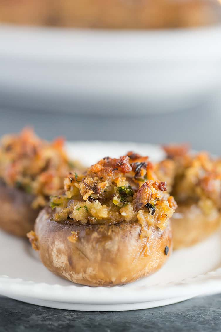 Three stuffed mushrooms on a small white plate.