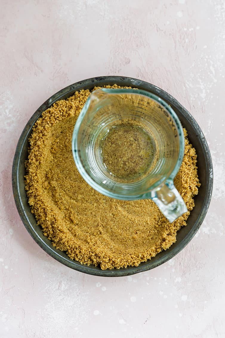 A glass measuring cup pressing down graham cracker crust.