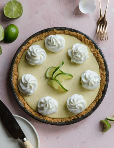 An overhead photo of key lime pie with whipped cream rosettes and lime garnishments.