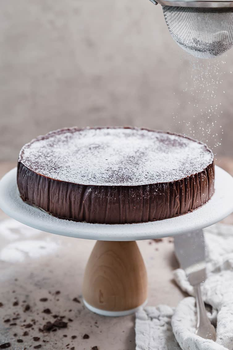 A round chocolate cake on a cake pedestal being dusted with powdered sugar.