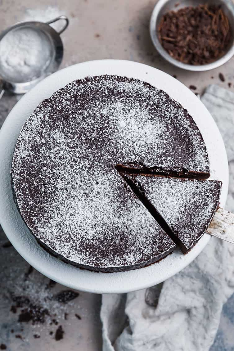 An overhead photo of flourless chocolate cake dusted with powdered sugar.