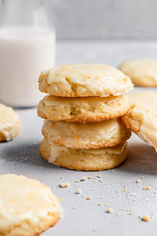 A stack of orange cookies with a glass of milk in the background.