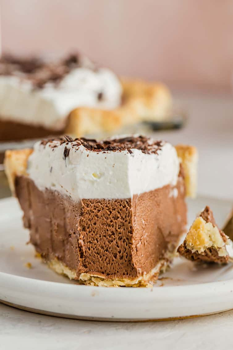 A closeup photo of a slice of French silk pie with a forkful removed.