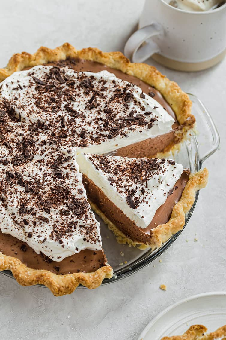 An overhead photo of French silk pie topped with whipped cream and chocolate curls.