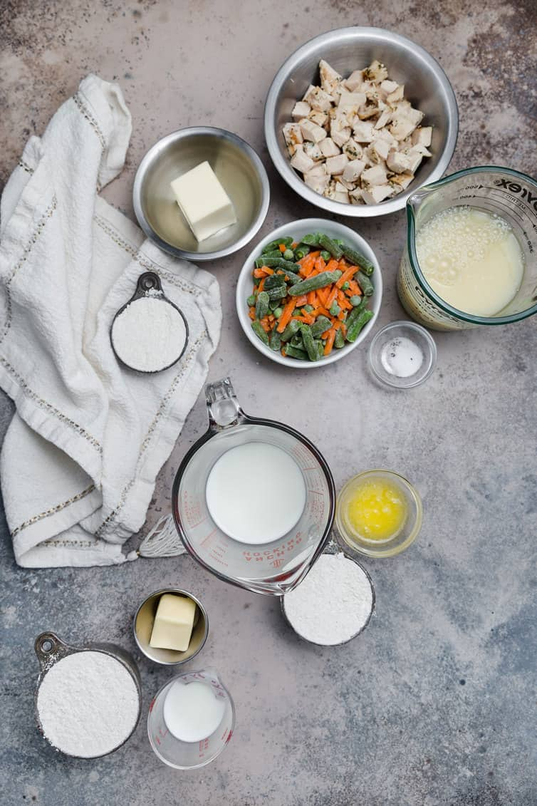 Bowls of chicken, vegetables, and other pot pie ingredients on a counter
