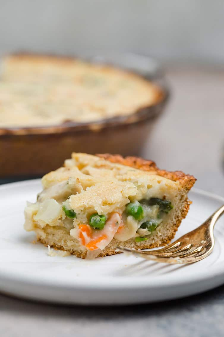 Partially eaten slice of pot pie on a plate with a fork