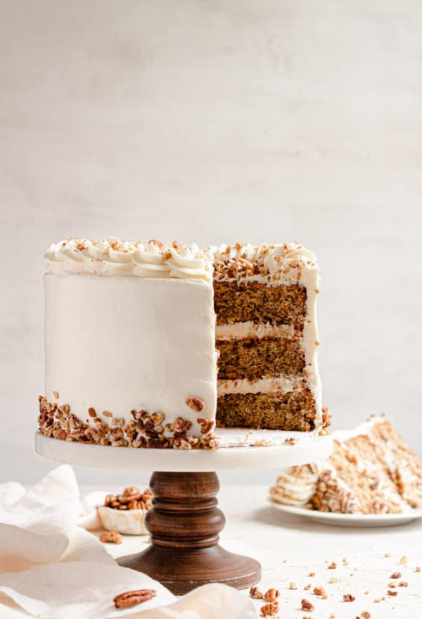 A hummingbird cake on a cake pedastal with slices removed.