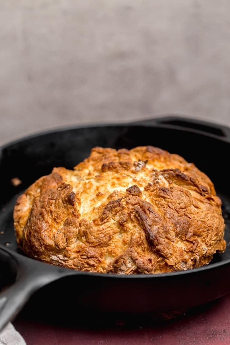 A loaf of baked Irish soda bread in a cast iron skillet.