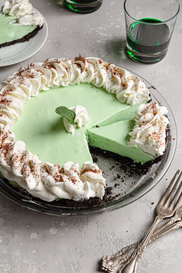 A grasshopper pie with a slice removed and another cut away from the whole pie.