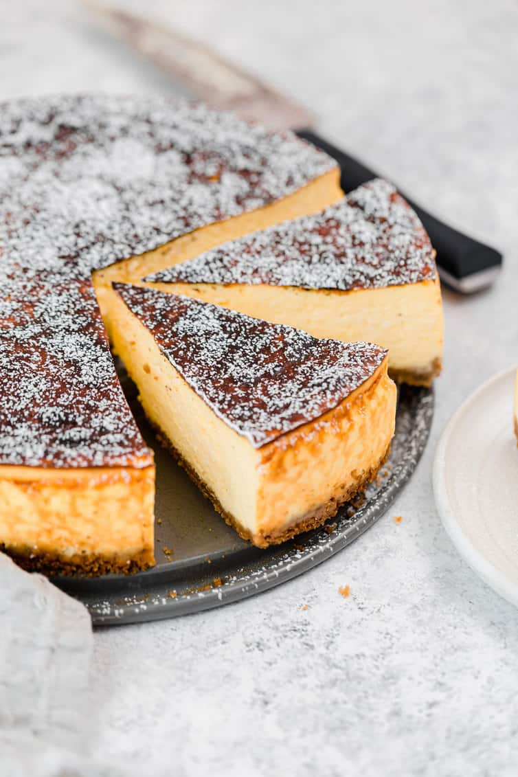 Slices of cheesecake on the springform pan, cut away from the whole cake.