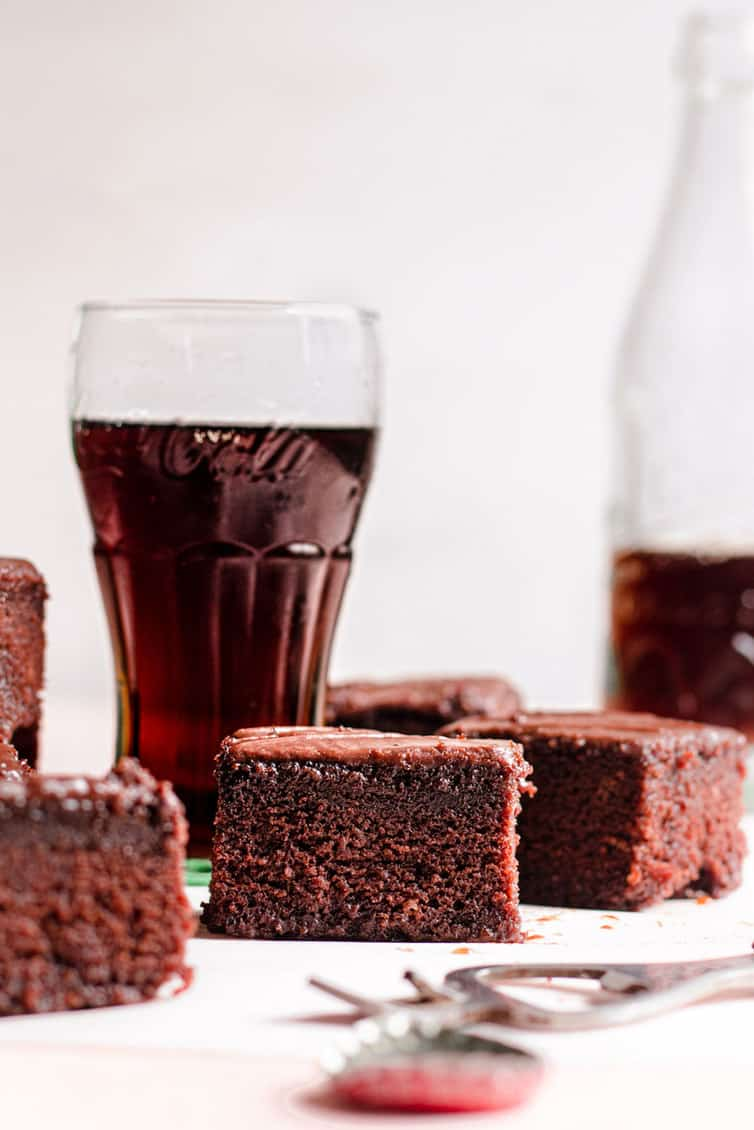 Pieces of chocolate cake in front of glasses of Coca Cola.