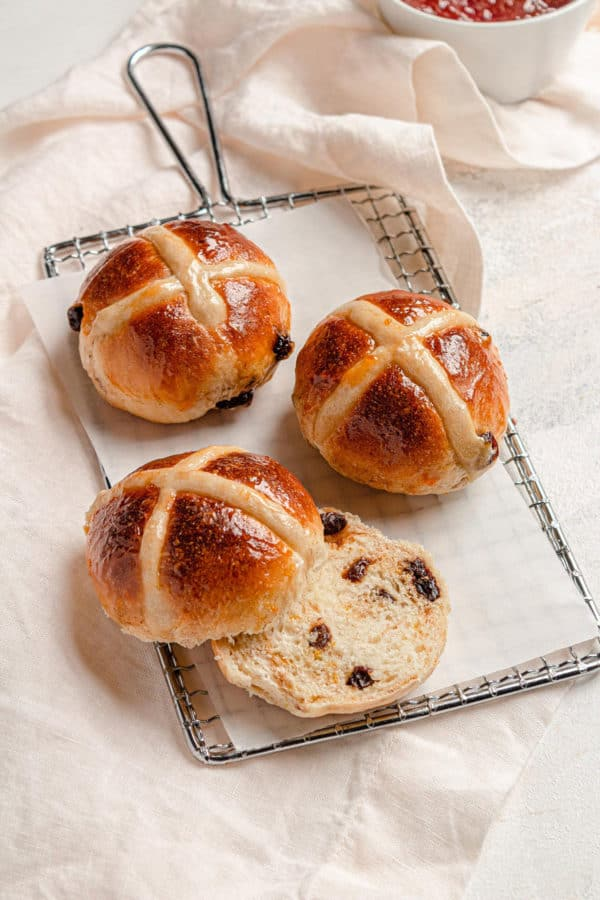 Three hot cross buns on a serving plate, one sliced in half.