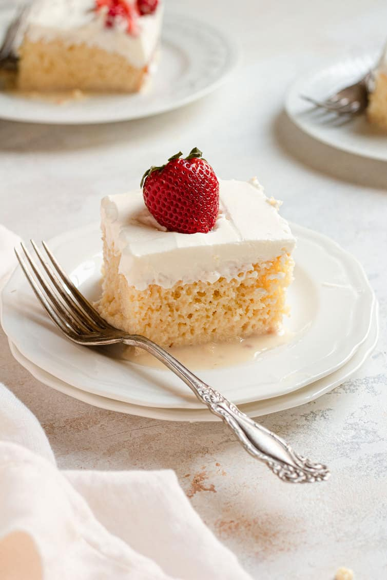 A piece of tres leches cake on a plate with a fork.