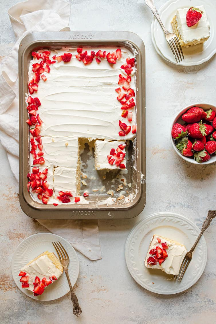 A pan of tres leches cake with three pieces removed and on plates.