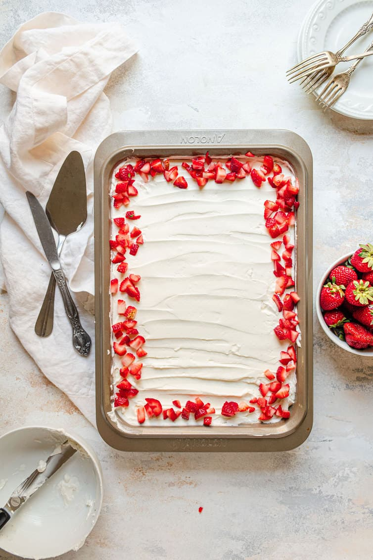 Pan of tres leches cake with strawberries around the border.