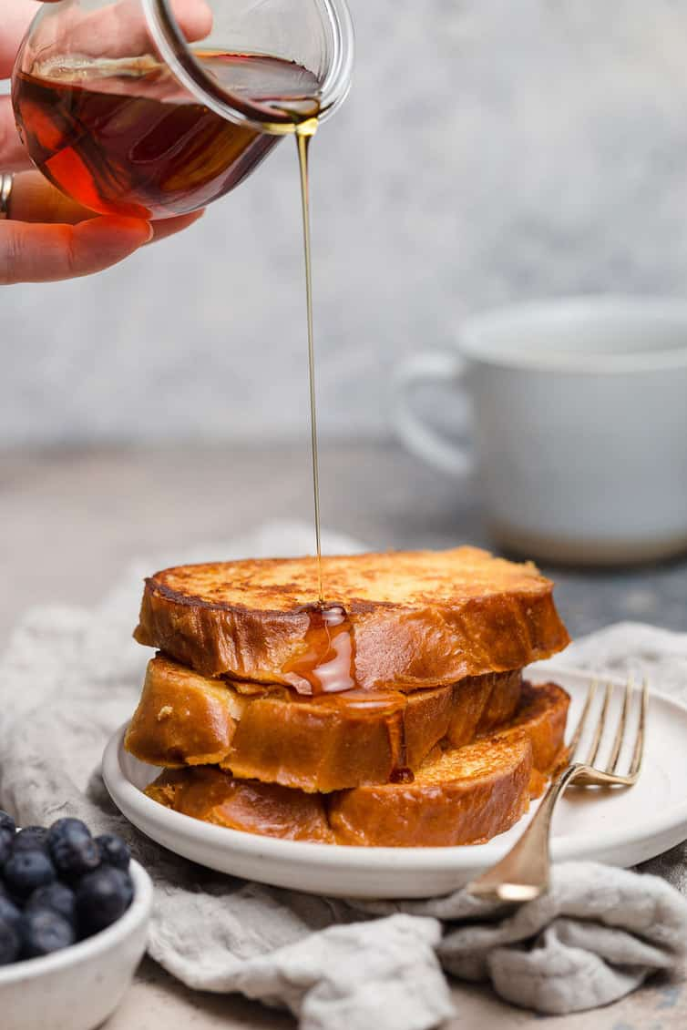 A stack of French toast with syrup drizzled on top.