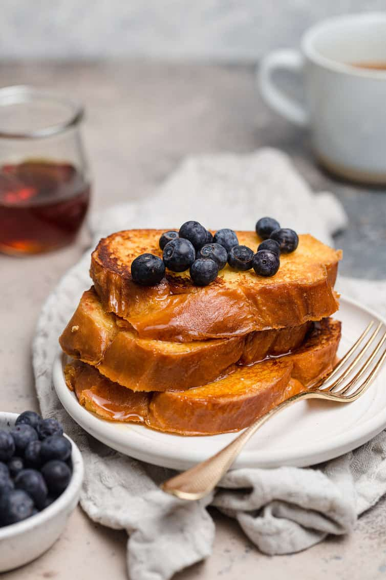 A stack of French toast on white plate with blueberries on top.