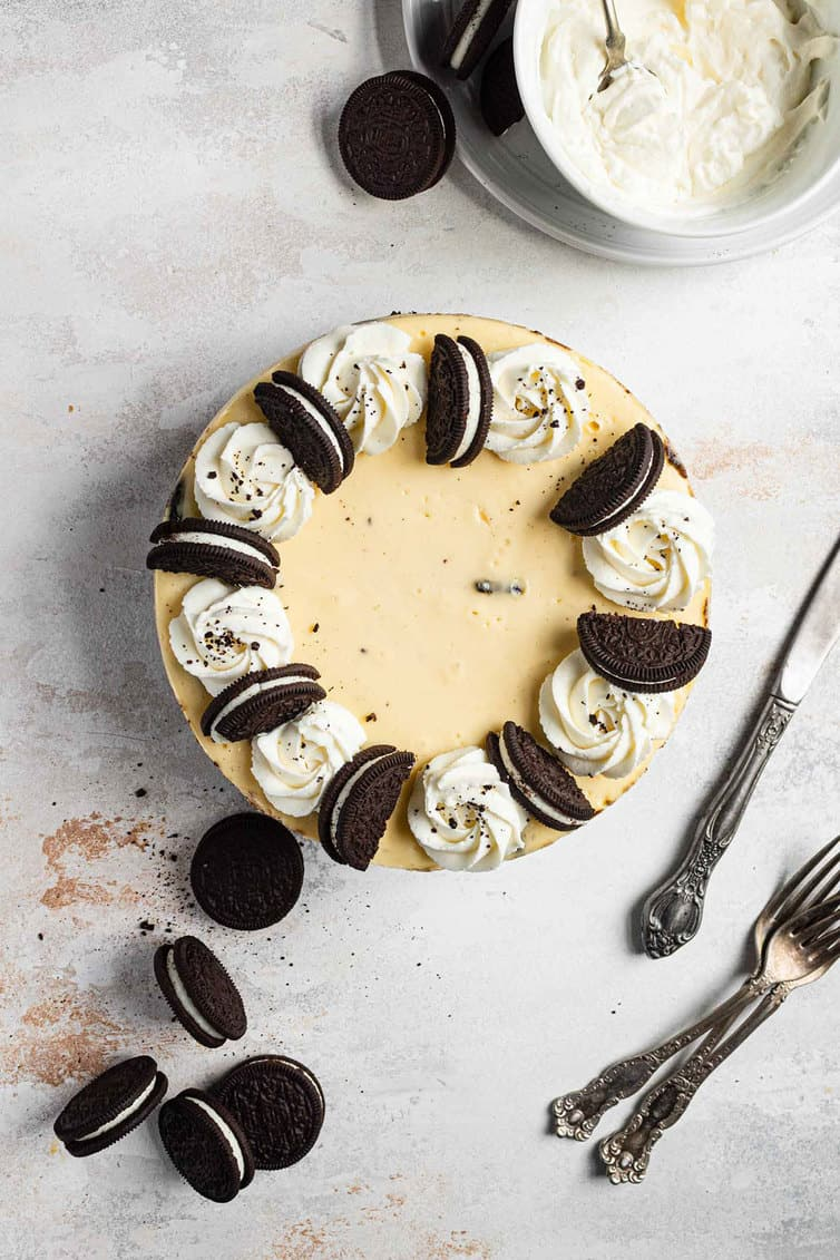 An overhead photo of Oreo cheesecake with silverware, Oreos and whipped cream around it.