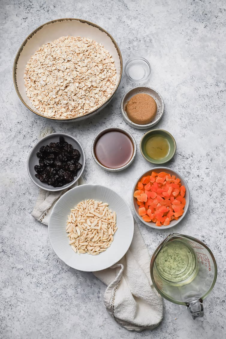 Ingredients for granola prepped in bowls on a counter.