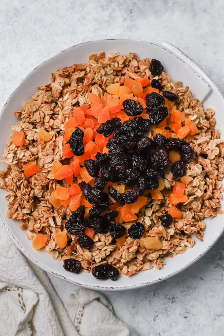 A bowl of granola with dried fruit on top.