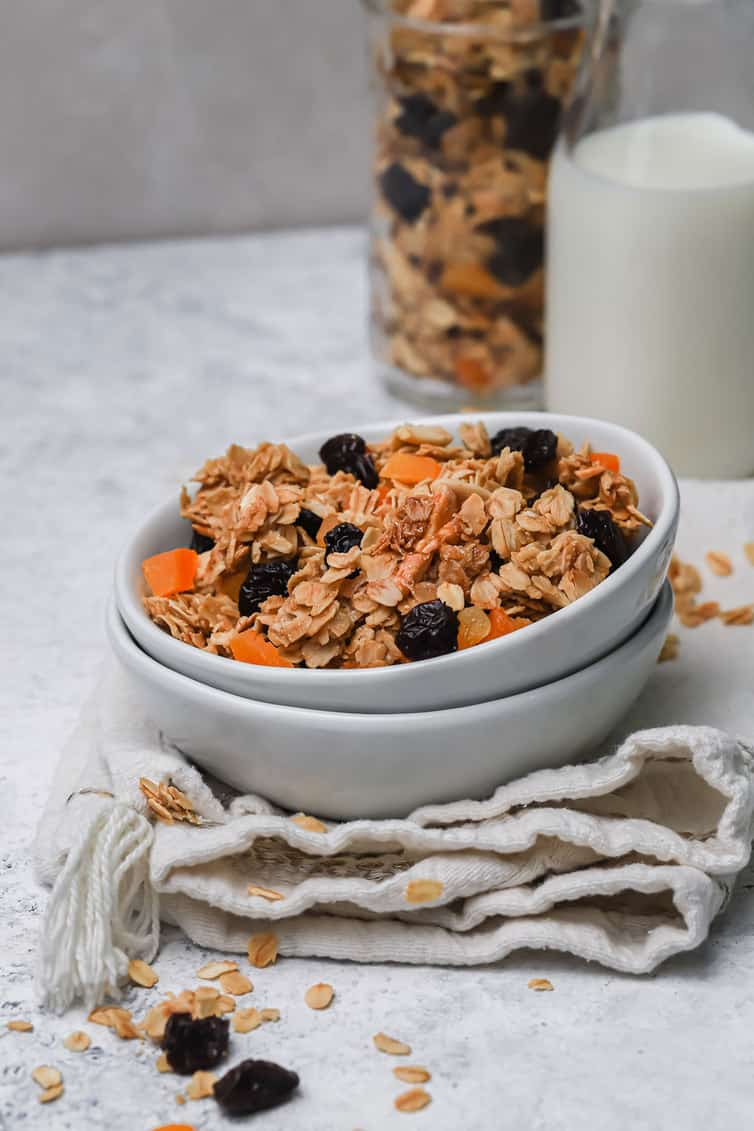 A bowl of granola with a glass of milk and jar of granola in the background.