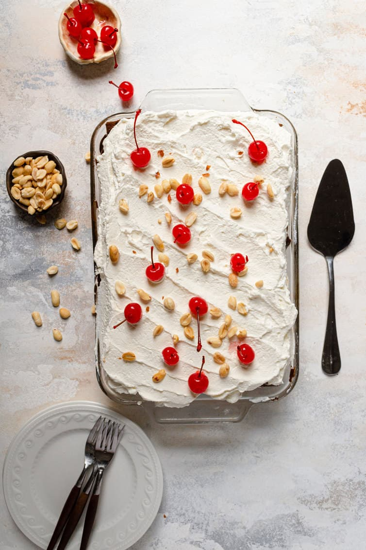 Ice cream sandwich cake with whipped cream, peanuts and cherries on top.
