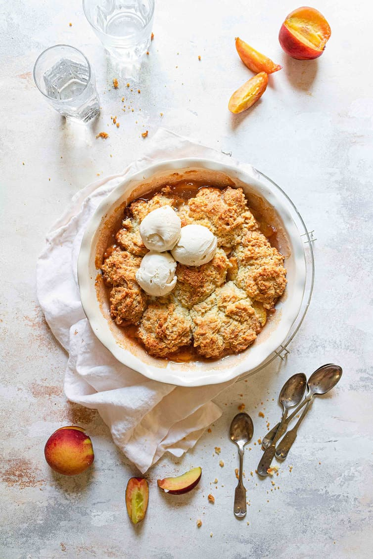 Baked peach cobbler with three scoops of ice cream on top.