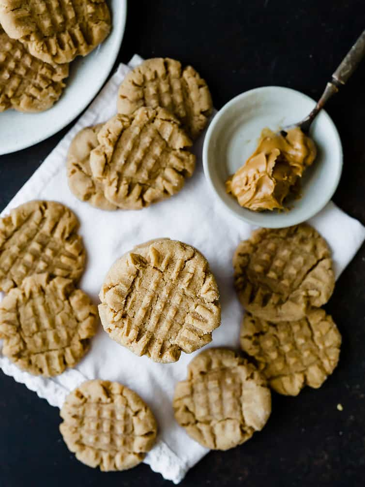 An overhead photo of baked peanut butter cookies with a spoonful of peanut butter.