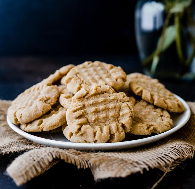A plate piled high with peanut butter cookies.