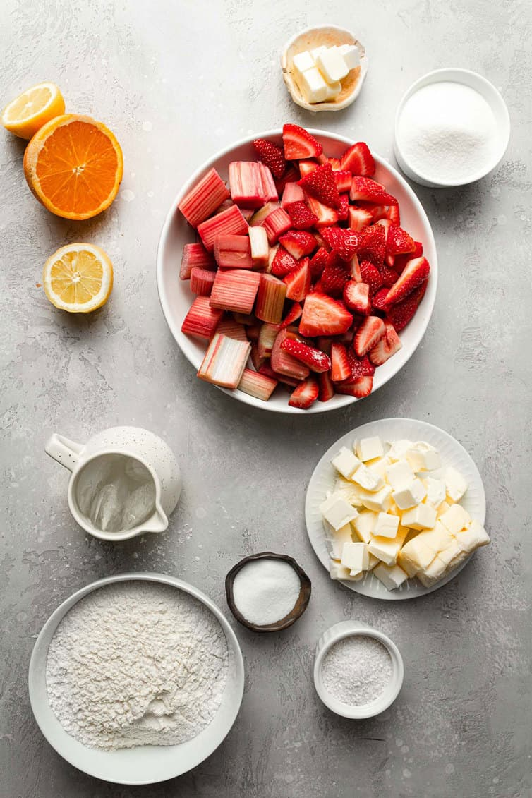 Ingredients for strawberry rhubarb pie prepped in bowls on counter.