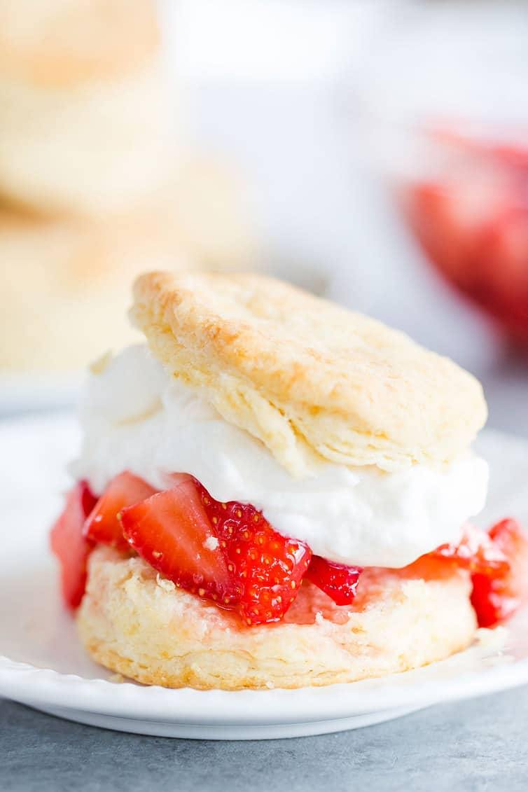 Assembled strawberry shortcake on a white plate.