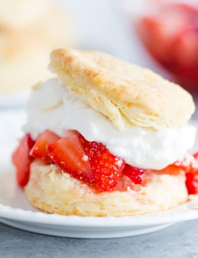 A biscuit filled with strawberries and whipped cream on a white plate.