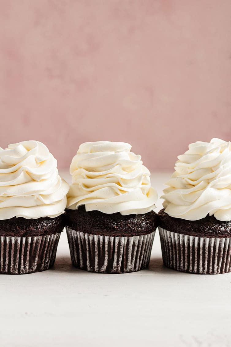 Three chocolate cupcakes with Swiss meringue buttercream piped on top.