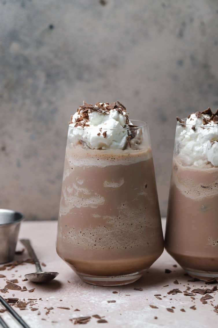 Two glasses of frozen hot chocolate topped with whipped cream and chocolate shavings.
