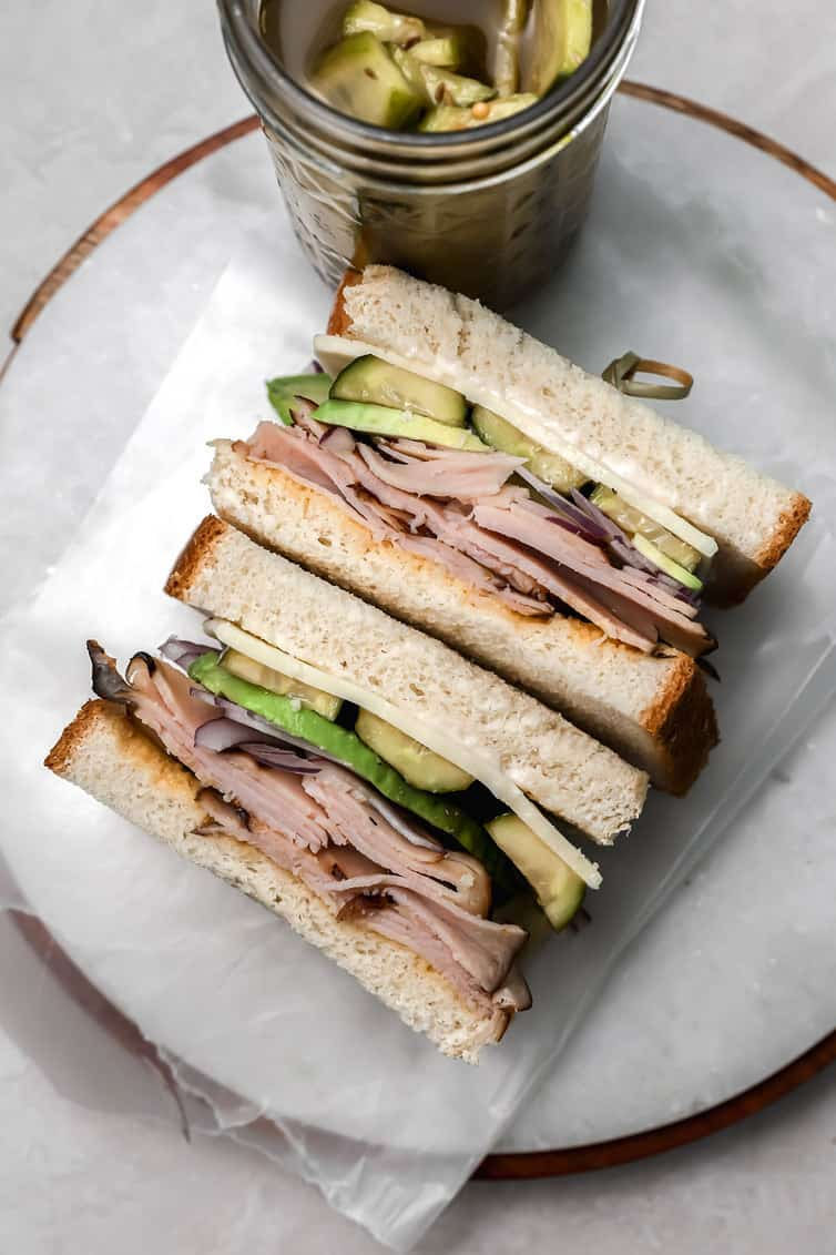Sandwich with a jar of pickles in the background.