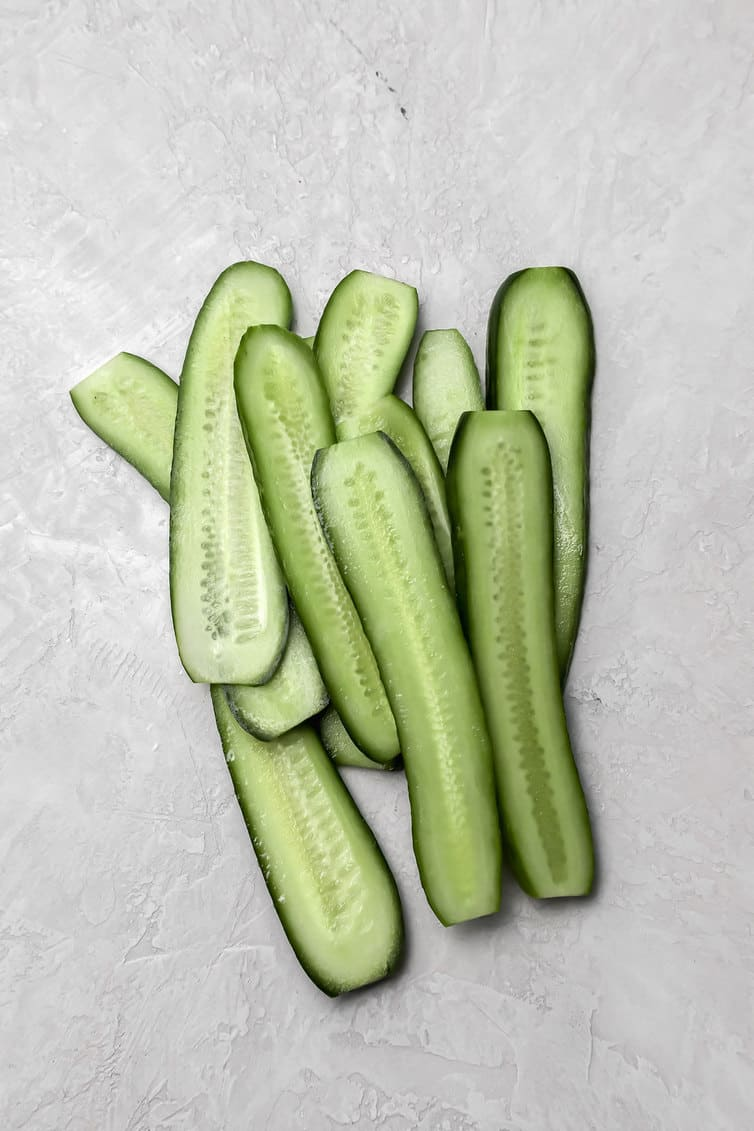 Pickling cucumbers sliced lengthwise.