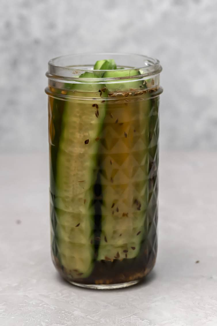 A jar of dill pickles without the lid on.