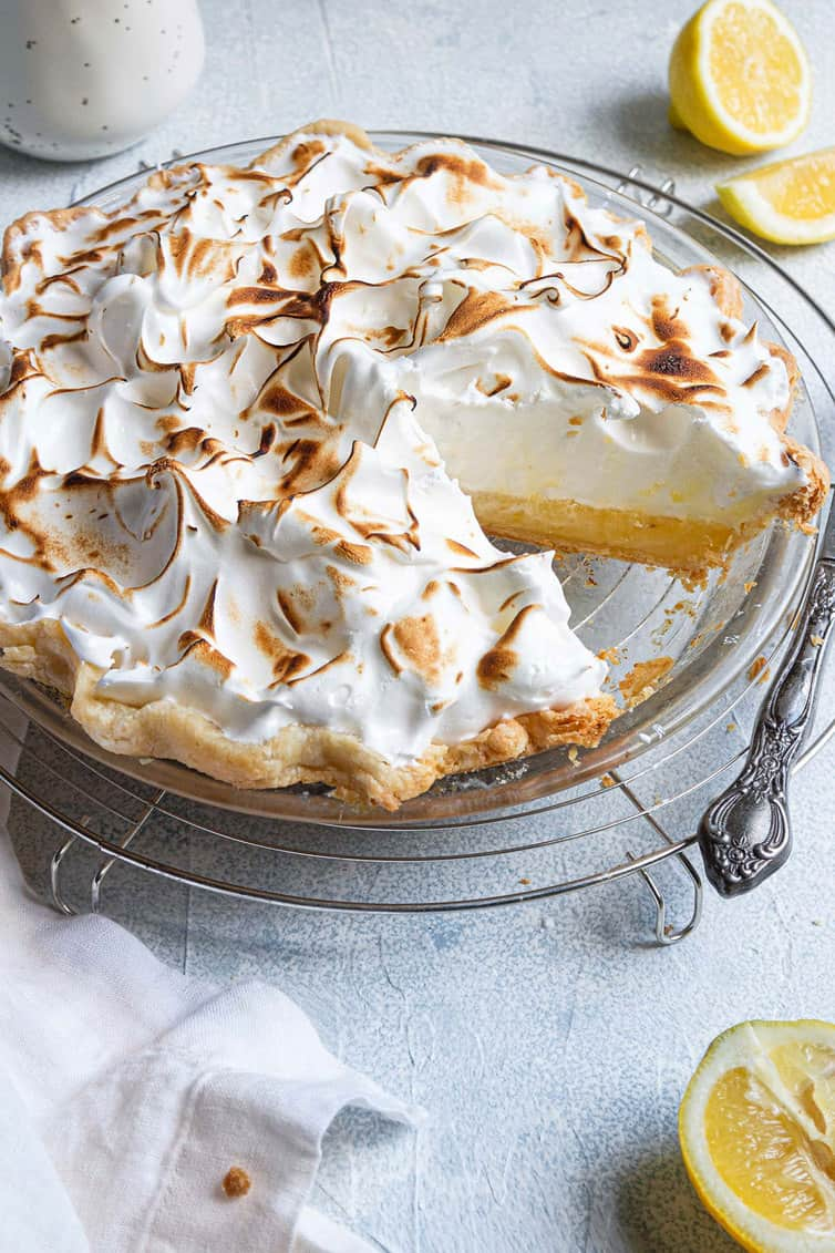 Lemon meringue pie in a glass pie plate with a slice removed.
