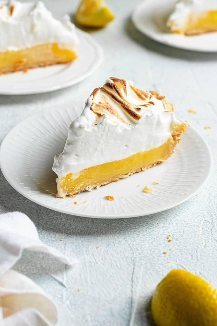 A slice of lemon meringue pie on a white plate.