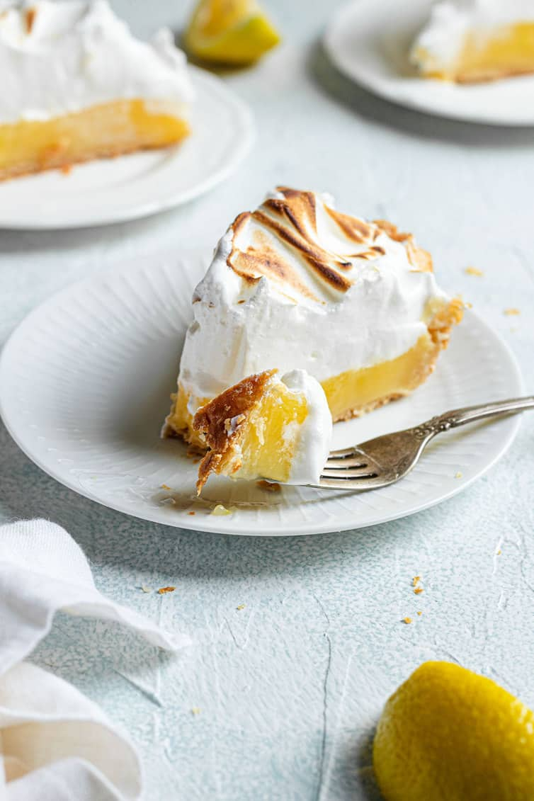 A slice of lemon meringue pie with a piece on a fork.