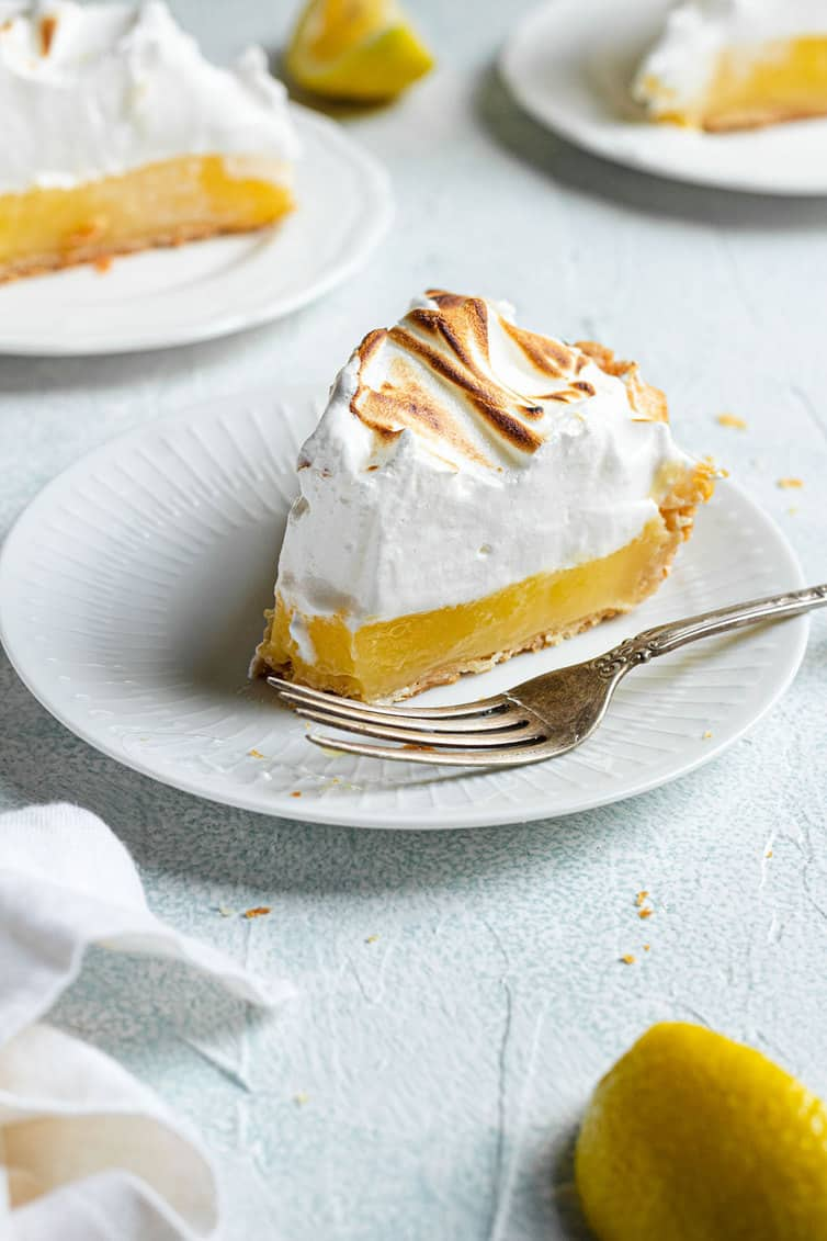 A slice of lemon meringue pie on a white plate with a fork.