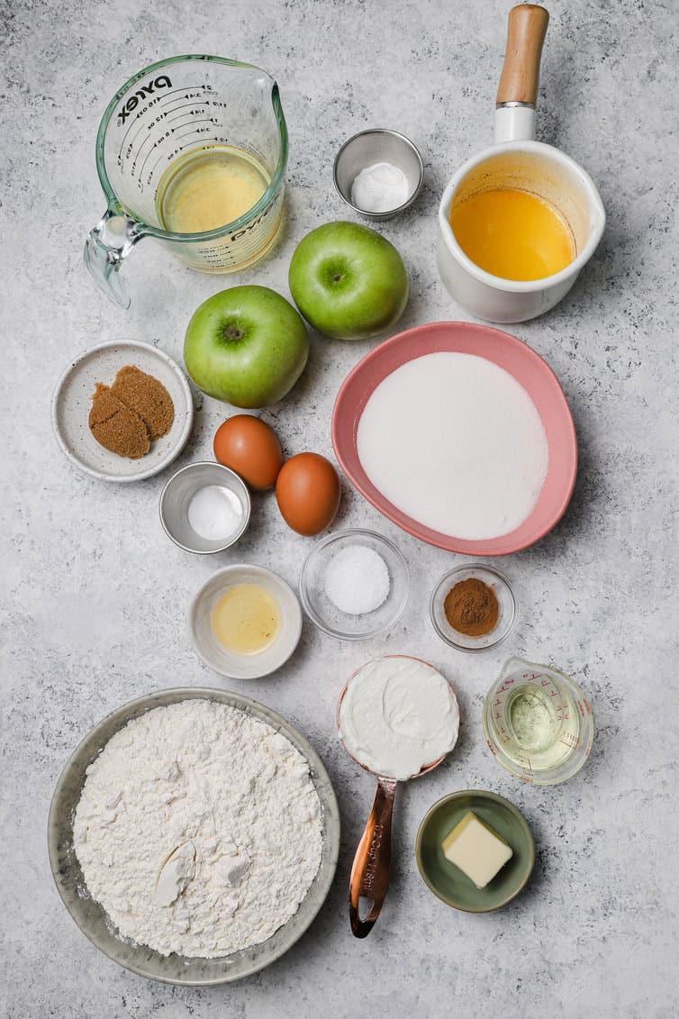 Ingredientes para muffins de maçã preparados em tigelas no balcão.