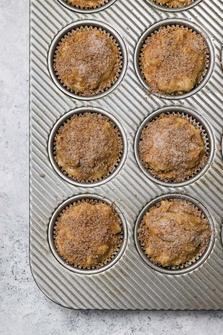 Apple muffin batter topped with cinnamon-sugar before baking.