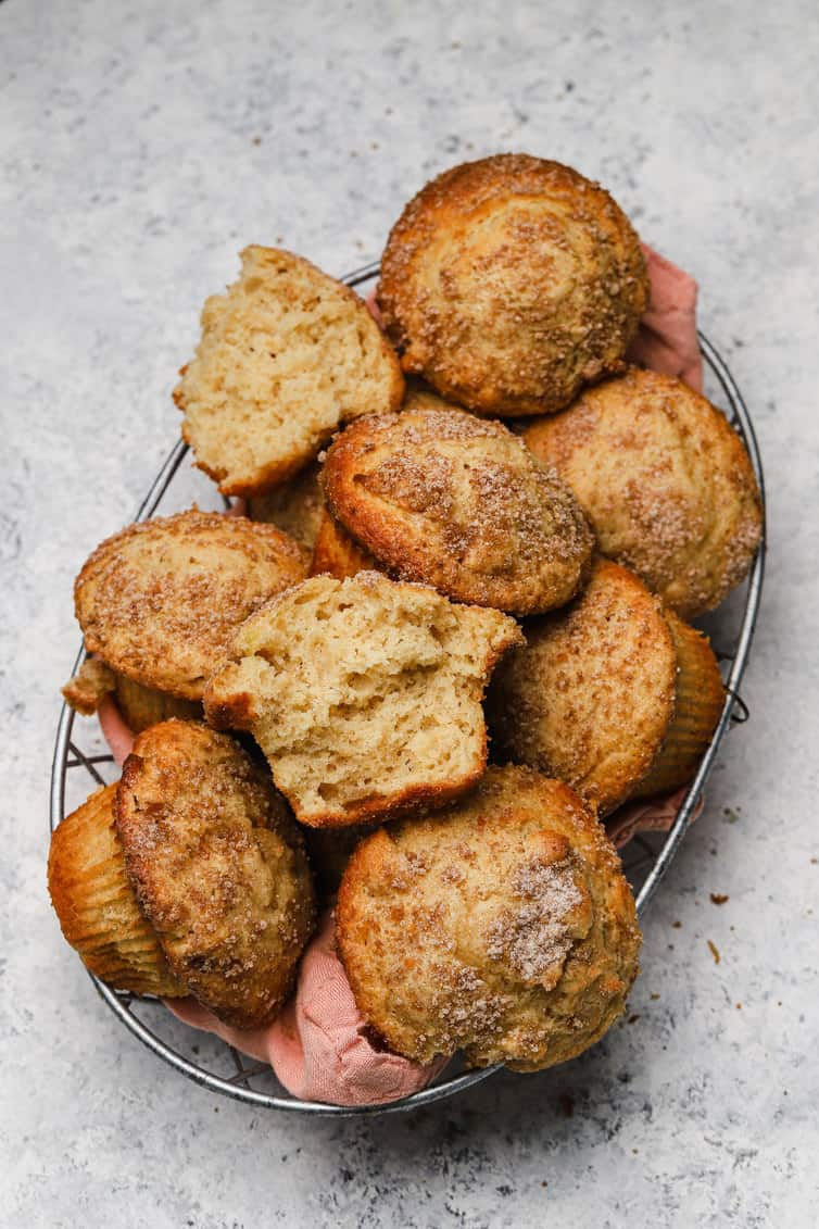 A basket of apple muffins with one split in half.
